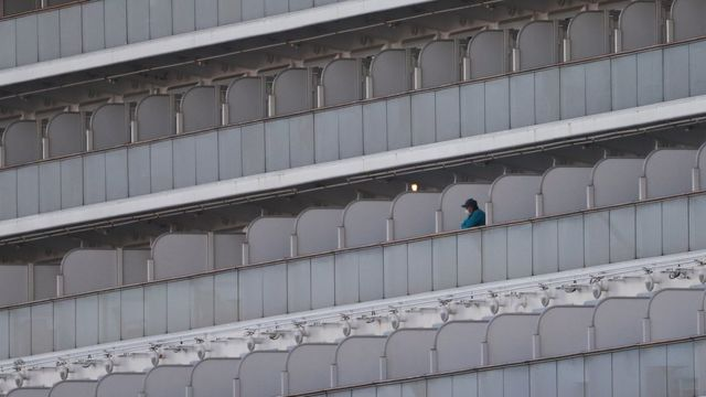 Someone wearing a face mask stands on the balcony of the quarantined Diamond Princess cruise ship
