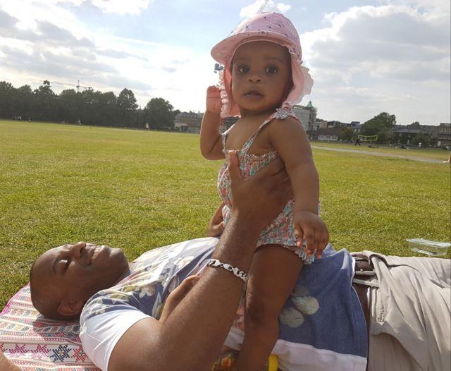 Elliott allongé sur l'herbe avec sa fille assise sur son ventre