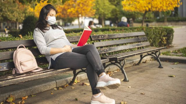 Young pregnant woman with protective face mask reading book sitting on a bench in city park in autumn.