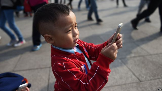 A young boy uses an iPhone to take photos in Tiananmen Square in Beijing on 30 September, 2014