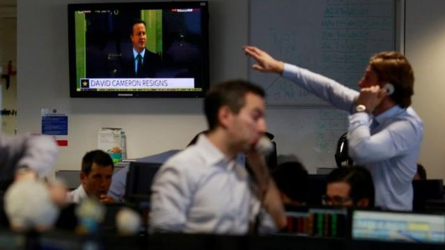 Operadores de mercado trabalham no centro de Londres enquanto David Cameron anuncia que deixará cargo