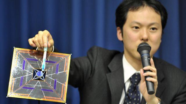 O cientista Yuichi Tsuda segurando um modelo do satélite IKAROS em uma conferência