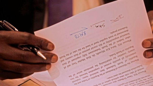 A picture taken on June 27, 2018 shows a document signed by Sudanese President Omar al-Bashir, South Sudan's President Salva Kiir Mayardit, and South Sudanese rebel leader Riek Machar, after the two South Sudanese arch-foes agreed in Khartoum to a 'permanent' ceasefire to take effect within 72 hours in their country
