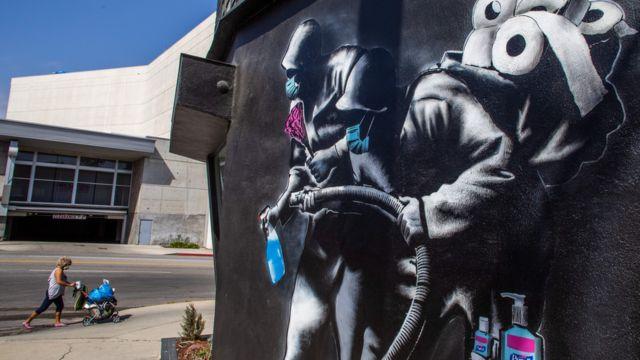 Un mural en California de dos personas con gel desinfectante y papel higiénico.