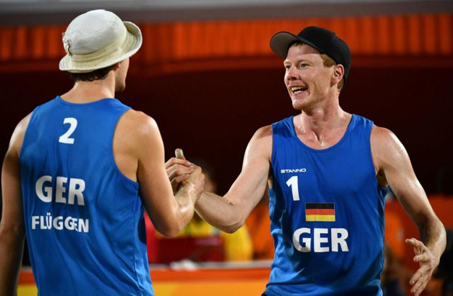 Germany's Lars Fluggen and Markus Bockermann celebrate after winning a point during the men's beach volleyball qualifying match between the Netherlands and Germany at the Beach Volley Arena in Rio de Janeiro on August 8, 2016
