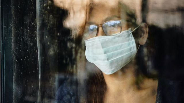 Woman looking through a wet window during lockdown because of Covid-19 - stock photo
