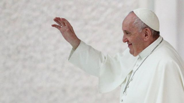 Aparecendo de perfil, Papa Francisco acena sorrindo