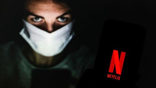 Chico con mascarilla mostrando celular con logo de Netflix