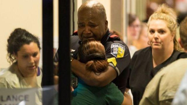 ベイラー大学医療センターで親類を慰める交通警官(7日、ダラス)