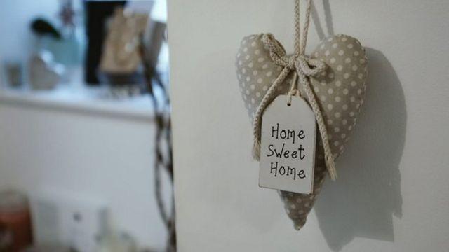 Un adorno en forma de corazón que dice hogar dulce hogar en la puerta de entrada a la casa de Alex.