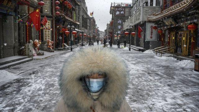 Một phụ nữ Trung Quốc đeo khẩu trang khi đi bộ trên đường phố vắng người ở Bắc Kinh