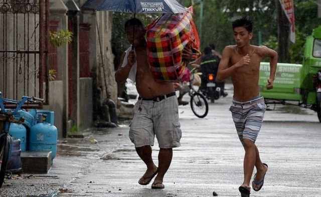 A resident carries his belongings to a safer place while another runs as rains started to pour, with Typhoon Mangkhut approaching the city of Tuguegarao, Cagayan province, north of Manila on September 14, 2018.