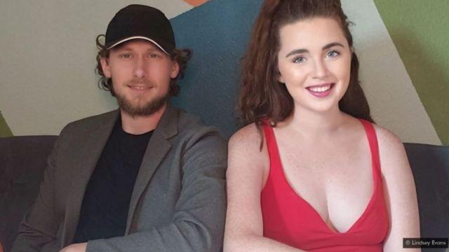 Lindsey e noivo posam sentados e sorrindo para foto, em ambiente interno