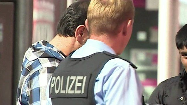 Back view of a German police officer in Munich talking to two men, possibly migrants (their faces partially hidden)
