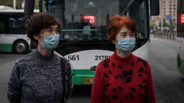 Dos mujeres en Wuhan esperan abordar un autobús después de la reanudación del servicio.