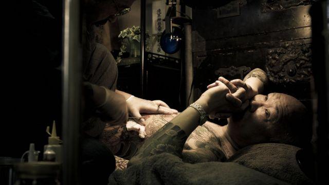 Un hombre siendo tatuado