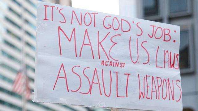 """Pancarta en la que se puede leer: """"No es tarea de Dios. Hagan leyes contra los fusiles de asalto"""""""