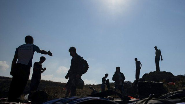 Migrants, who came across Turkey, make land from an overloaded rubber dinghy as they arrive at the coast