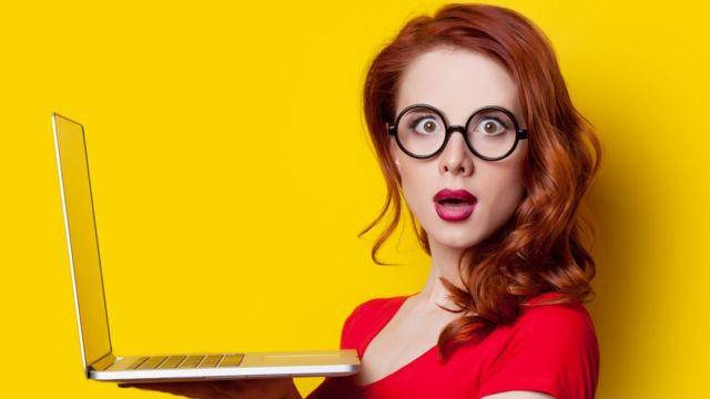 Mujer joven sosteniendo computadora.