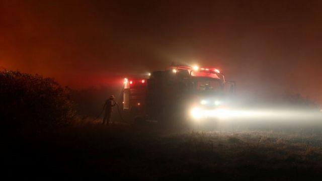 Caminhão e bombeiro no meio da estrada à noite