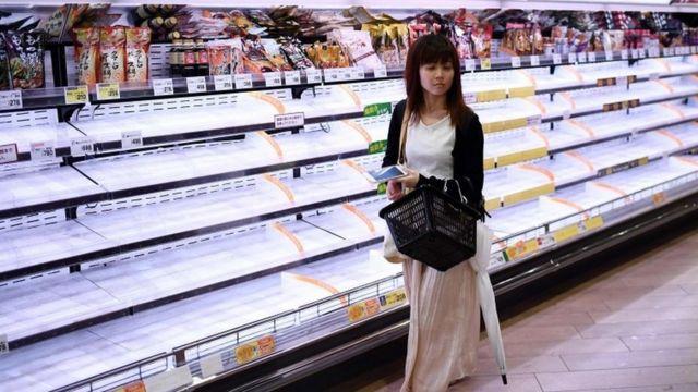 Женщина в продовольственном магазине в Токио (12 октября 2019 года)