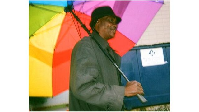 Hombre con una sombrilla de colores.
