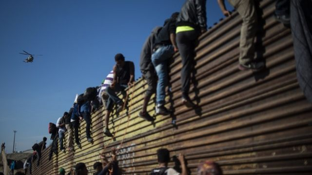 A group of Central American migrants -mostly Hondurans- climb the border fence between Mexico and the United States, near El Chaparral border crossing, in Tijuana, Baja California State, Mexico, on November 25, 2018.