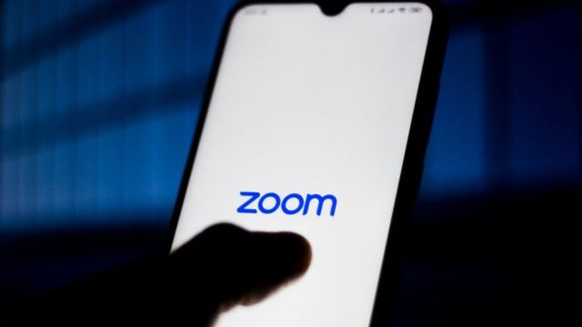 Zoom Meetings logo is seen displayed on a smartphone