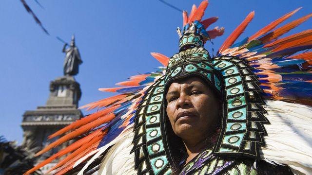 Una mujer vestida con un traje azteca