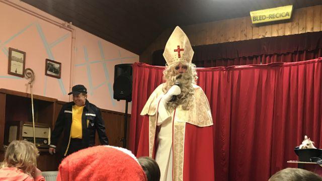 Homem caracterizado de São Nicolau entrega presentes para crianças em festa tradicional em Bled, na Eslovênia