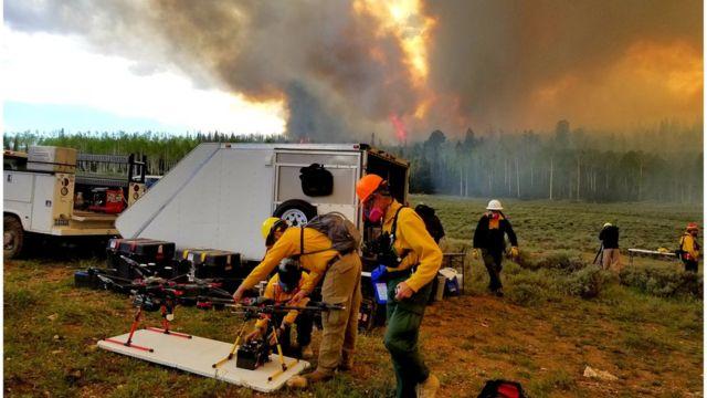 Cientistas paramentados e com equipamentos se preparam para fazer um drone decolar em frente a um incêndio florestal que solta muita fumaça