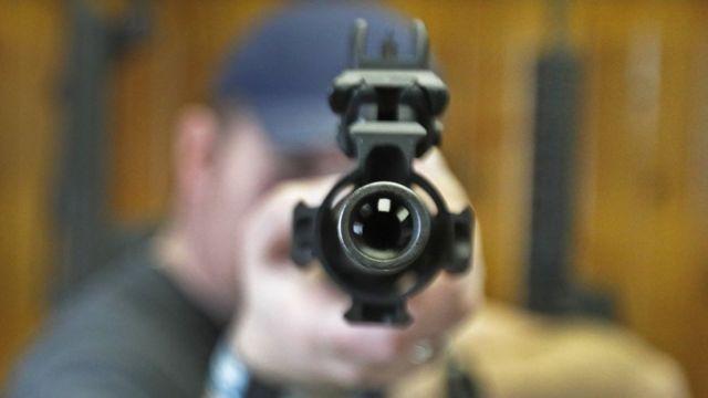 A man pointing a gun at the camera