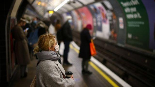Pessoas de máscara na plataforma do metrô; em primeiro plano uma mulher loira de máscara segura um café na mão