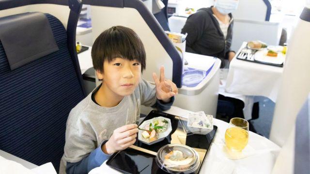 Criança comendo refeição em primeira classe de avião parado da ANA