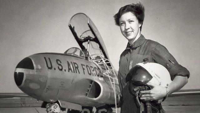 Imagen en blanco y negro de Wally Funk con un avión de la Fuerza Aérea de EE.UU. detrás