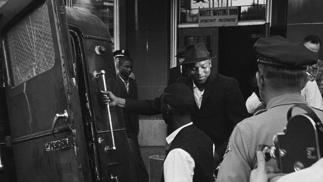 """Passageiros negros sendo expulso de uma sala de espera """"para brancos"""" em uma rodoviária em Jackson, no Mississippi"""