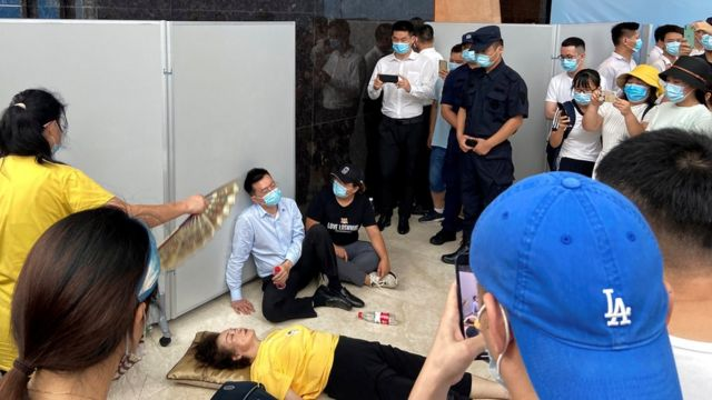 恒大财富执行董事兼总经理杜亮(中)瘫坐在一位晕倒的女士旁边(13/9/2021)