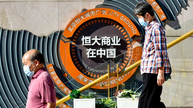 People pass in front of Evergrande group's blueprint for development in China at Evergrande city square, Chaoyang District