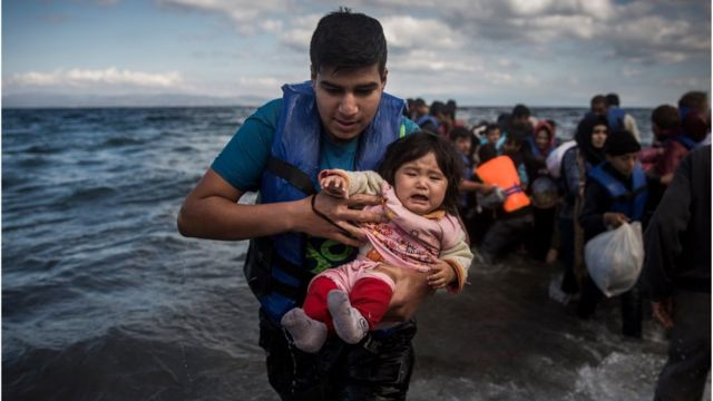 A man holding a baby disembarks from a dinghy after arriving from a Turkish coast to the northeastern Greek island of Lesbos, Sunday, Oct. 25, 2015.