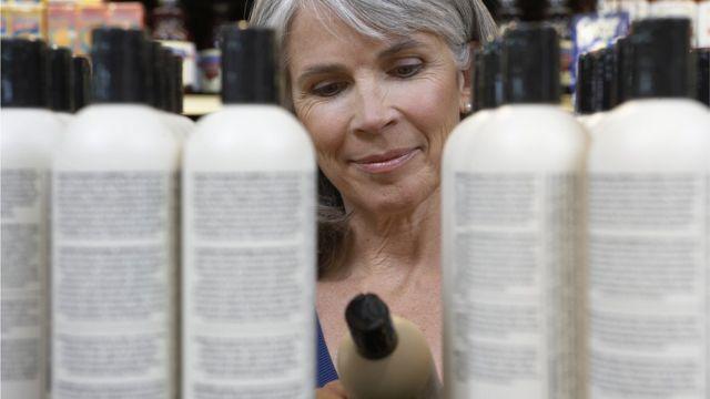 Mujer mirando frascos de champú