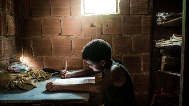 Menino estuda em frente a uma janela, em uma casa de tijolos aparentes