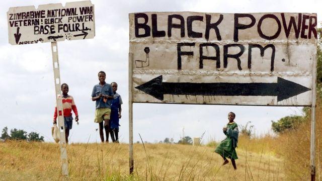 """Watoto wa shule wakiwa kwenye shamba moja kilomita 40 mashariki mwa Harare lililoitwa """"Black Power Farm"""" yaani shamba la nguvu ya weusi , na wapiganaji wa zamani ambao walinyakuwa shamba hilo tarehe 21 Juni 2000"""