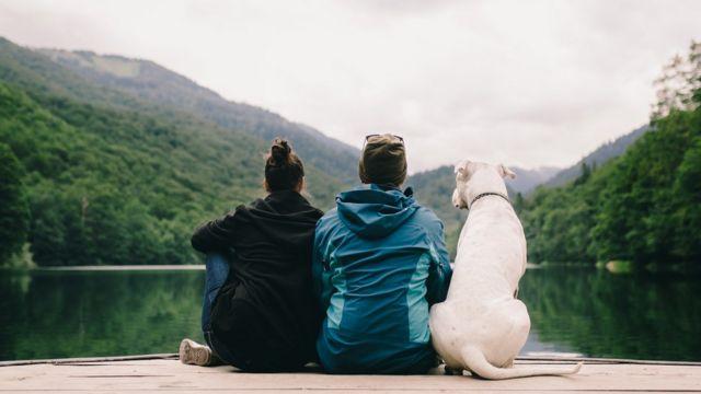 Una mujer, un hombre y un perro sentados en un muelle.