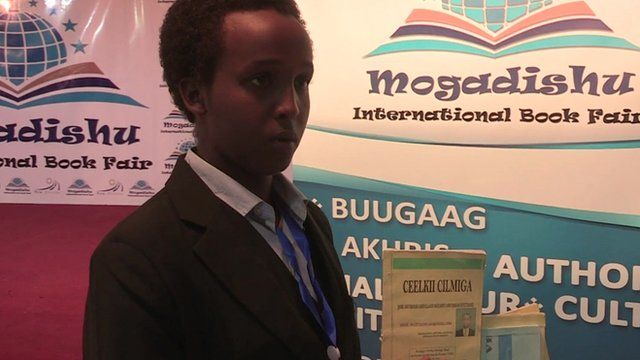 16-year-old Somali author Abukar Abdullahi Mohamed holding some of his books at the Mogadishu International Book Fair