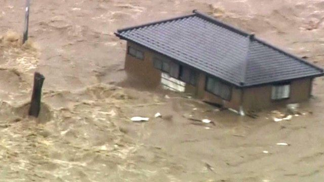 A house is swept down steam by floodwater in Japan