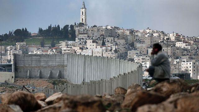 Hombre palestino sentado cerca de la controvertida barrera de separación de Israel en Jerusalén.