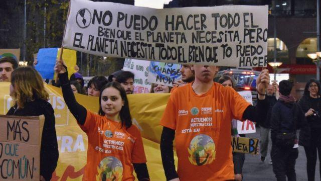 """Ariana Palombo con un cartel que dice """"No puedo hacer todo el bien que el planeta necesita, pero el planeta necesita todo el bien que yo pueda hacer""""."""