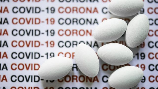 Comprimidos sobre fundo com as palavras covid-19 e corona
