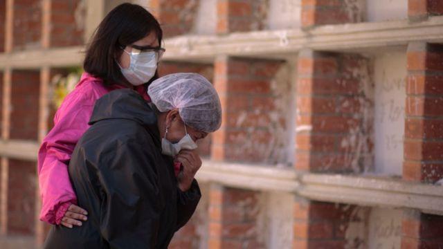 امرأتان ترتديان أقنعة الوجه تنوحان في مقبرة في لاباز ، بوليفيا