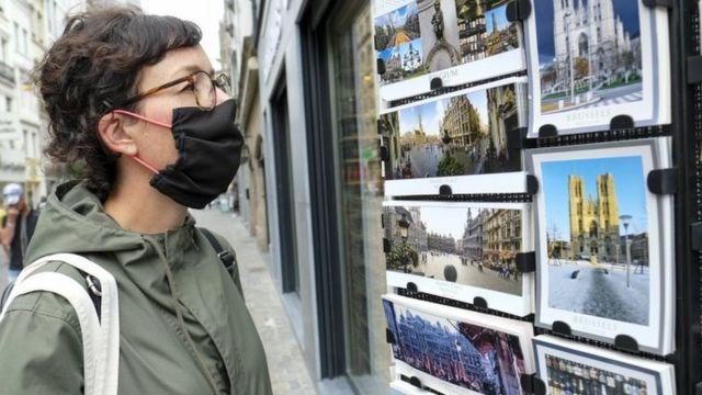 Mulher observa cartões postais na Bélgica